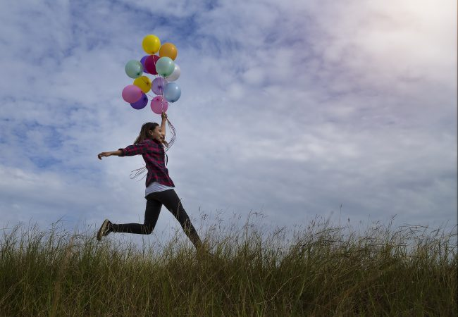Beautiful girl holding balloons running in prairie grass. On a clear day